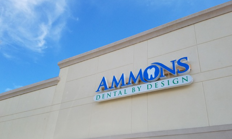 Blue, green, and white sign saying Ammons Dental By Design with a tooth logo for the O on a tan building