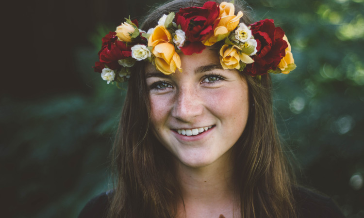 Dark-haired young woman smiles while wearing a crown of red, yellow, and white flowers in front of greenery