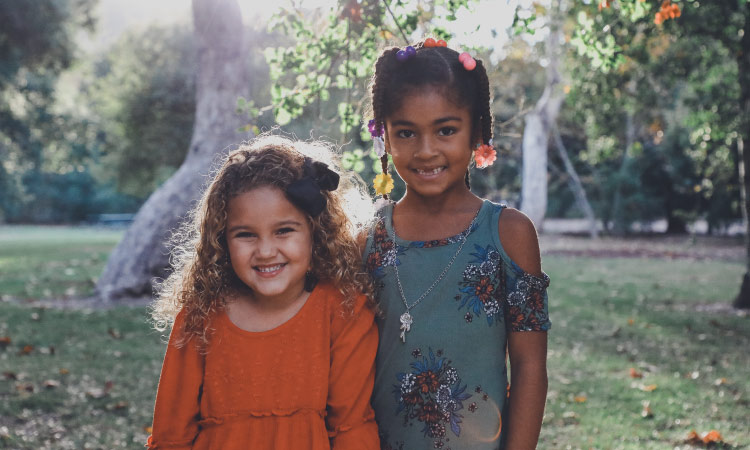 Curly haired young girl in an orange dress stands next to a dark-haired older girl in a blue dress as they smile outside