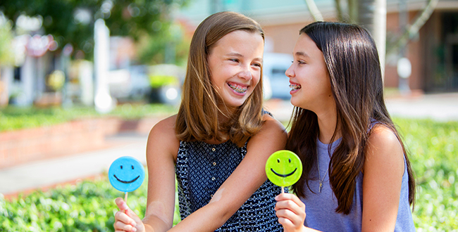Two young girls with braces smiling at each other