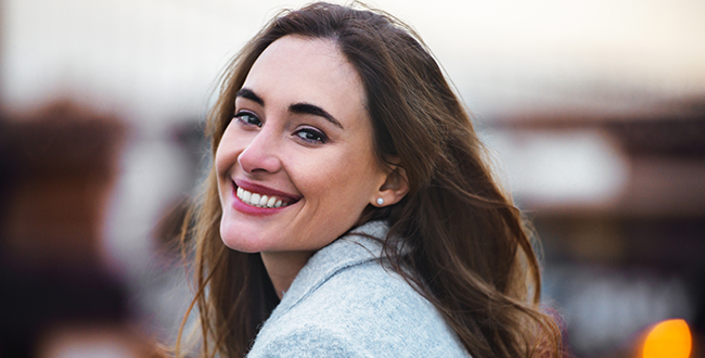 A young woman looks over her shoulder smiling at the camera