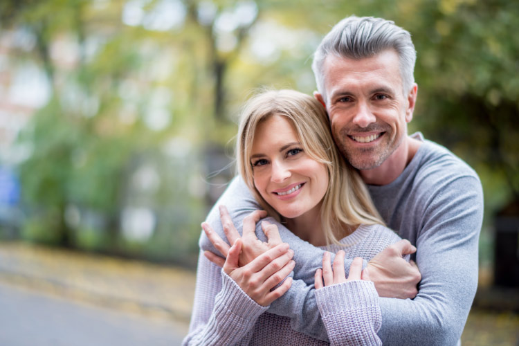 A husband and wife embrace outside and smile with dental implants